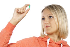 Girl looks at the pill Royalty Free Stock Images