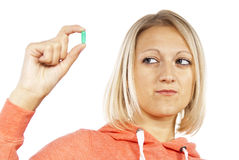 Girl looks at the pill and doubts Royalty Free Stock Images