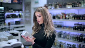 Girl looks at products from the shelf in store stock video