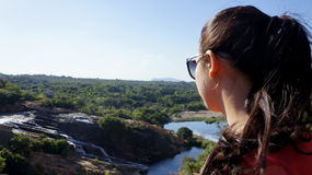 The girl looks at the river. A girl in sunglasses looks at the river and forest Royalty Free Stock Photo