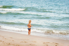 Girl looks at the sea. Little girl looks at the sea royalty free stock photo