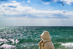 The girl looks at the sea. Past flying seagull. Stock Photo