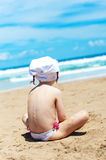 Girl looks at the sea sitting on the sand Royalty Free Stock Photos