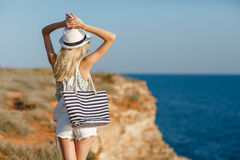 The girl looks at the sea, standing on a rock Stock Photography