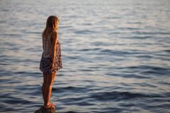 The girl looks at the sea sunset stock photos