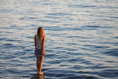 The girl looks at the sea sunset royalty free stock images