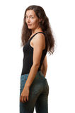 A girl looks from a shoulder. A girl with long ringleted hairs in black tank and jeans looks from her shoulder Stock Photo