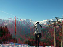 Girl looks at the snow-capped mountains stock photography