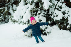Girl looks at a snowy branch. Little girl looks at a snowy branch royalty free stock photos