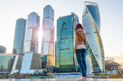 The girl looks at the sun and skyscrapers in the megalopolis Stock Photos