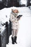 The girl looks in the tablet computer in a winter park. There is Stock Images