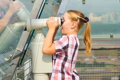 A girl looks through a telescope Stock Images
