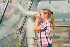 A girl looks through a telescope Royalty Free Stock Image