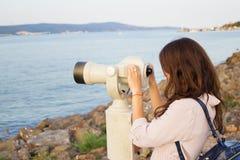 The girl looks through the telescope at the sea.  Stock Photos