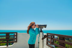 Girl looks through a telescope on the sea background Royalty Free Stock Images