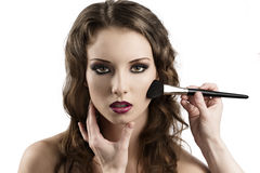 Girl looks in to the lens, getting made-up Stock Photo