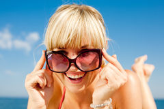 Girl looks on top of sunglasses Stock Photos