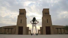 Girl looks at tower, amphitheater in the desert stock video