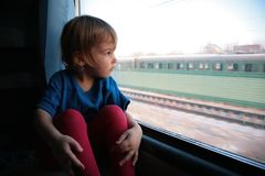 Girl  looks in train`s window Stock Photography
