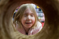 Girl looks through the tube. Closed eyes. Stock Photos