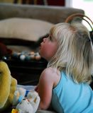 Girl looks up. Toddler girl with blond hair looks up from playing with her stuffed animals royalty free stock photo