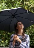 Girl looks up at her umbrella stock image
