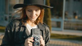 Girl Looks at Vintage Camera. Fair hair caucasian girl, in stylish black hat, looking at vintage camera before modern building, slowmotion in sunset stock footage