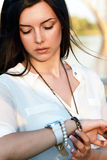 Girl looks at watch Stock Images