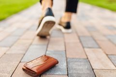 The girl lost a leather wallet with money on the street. Close-up of a wallet lying on the sidewalk and legs of a departing girl stock images