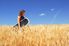 Girl lost in Wheat Field. Pretty Girl in Durum Wheat Field, holding wakeboard Royalty Free Stock Photos