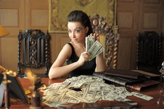 Girl and a lot of dollars Royalty Free Stock Image