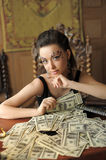 Girl and a lot of dollars Royalty Free Stock Photos