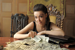 Girl and a lot of dollars Stock Images