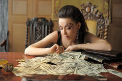 Girl and a lot of dollars Stock Photos