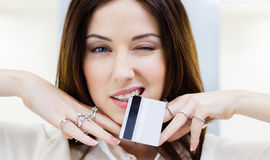 Girl with lots of rings on hands keeps credit card. Concept of wealth and luxurious life Royalty Free Stock Image