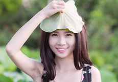 Girl with lotus leaf Stock Photography