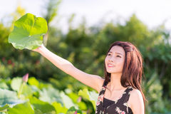 Girl with lotus leaf Stock Images