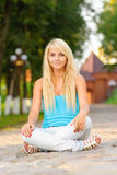 Girl in lotus pose. Beautiful blonde sits in lotus pose in city park Stock Photo
