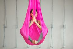 Girl lotus pose aerial antigravity yoga. Woman sits in hammock stock image