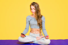 Girl in lotus pose listening to music Royalty Free Stock Image