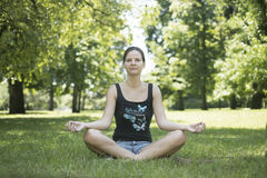 Girl in lotus pose in the park. Royalty Free Stock Photos