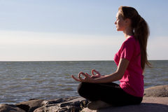 Girl in lotus pose sitting near sea Stock Photo