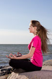 Girl in lotus pose sitting near sea Stock Photos