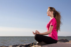 Girl in lotus pose sitting near sea Royalty Free Stock Photo