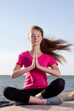 Girl in lotus pose sitting near sea Stock Images