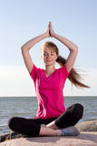 Girl in lotus pose sitting near sea Royalty Free Stock Image