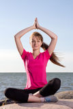 Girl in lotus pose sitting near sea Royalty Free Stock Photography