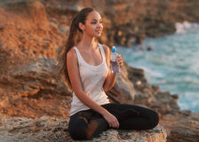 Girl in lotus pose. At sunset and holding water Stock Photo