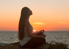 Girl in lotus pose at sunset. Girl in the lotus position meditating on the beach at sunset Royalty Free Stock Images