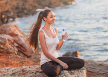 Girl in lotus pose at sunset. A young girl holds a subtle bottle of water in hand, sitting in a lotus position on a rock by the sea in the rays of the setting Royalty Free Stock Photo